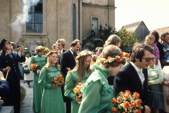 1976:   At a royal wedding in Germany, the bridesmaids sported high-necked green dresses accented with flower crowns adorned with baby's breath, a trademark of bridesmaid fashion in the '70s.
