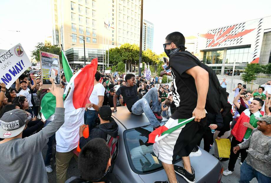 Protesters climb atop a car stopped in traffic as a crowd marches near the venue where Republican presidential candidate Donald Trump was speaking during a rally in San Jose, California on June 2, 2016. Protesters who oppose Donald Trump scuffled with his supporters on June 2 as the presumptive Republican presidential nominee held a rally in California, with fistfights erupting and one supporter hit with an egg. / AFP PHOTO / JOSH EDELSONJOSH EDELSON/AFP/Getty Images Photo: JOSH EDELSON, AFP/Getty Images