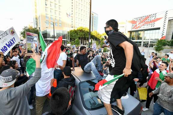 Protesters climb atop a car stopped in traffic as a crowd marches near the venue where Republican presidential candidate Donald Trump was speaking during a rally in San Jose, California on June 2, 2016.  Protesters who oppose Donald Trump scuffled with his supporters on June 2 as the presumptive Republican presidential nominee held a rally in California, with fistfights erupting and one supporter hit with an egg. / AFP PHOTO / JOSH EDELSONJOSH EDELSON/AFP/Getty Images