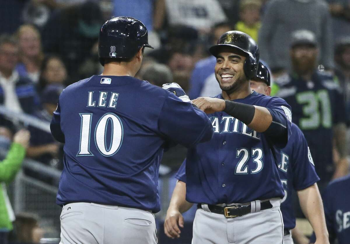 Seattle Mariners' Dae-Ho Lee is greeted by Nelson Cruz after hitting a three-run home run against the San Diego Padres during the sixth inning of a baseball game Thursday, June 2, 2016, in San Diego. (AP Photo/Lenny Ignelzi)