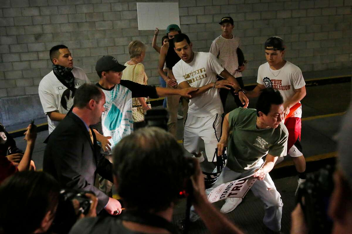 Anti-Trump protesters pursue Trump supporters into the garage where many of them parked next to the convention center where presidential candidate Donald Trump held a campaign rally June 2, 2016 in downtown San Jose, Calif.