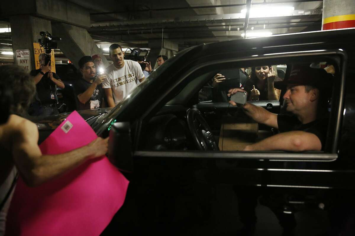 A Trump supporter takes video from his car as anti-Trump protesters rock it back and fourth in the parking garage next to the convention center where presidential candidate Donald Trump held a campaign rally June 2, 2016 in downtown San Jose, Calif.