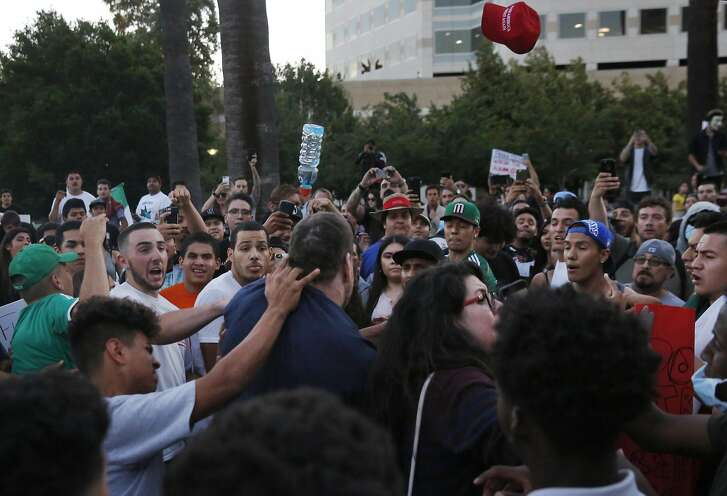 A Trump supporter lashes out after being surrounded by a crowd of anti-Trump protesters and having his hat snatched off his head near the convention center where presidential candidate Donald Trump held a campaign rally June 2, 2016 in downtown San Jose, Calif.