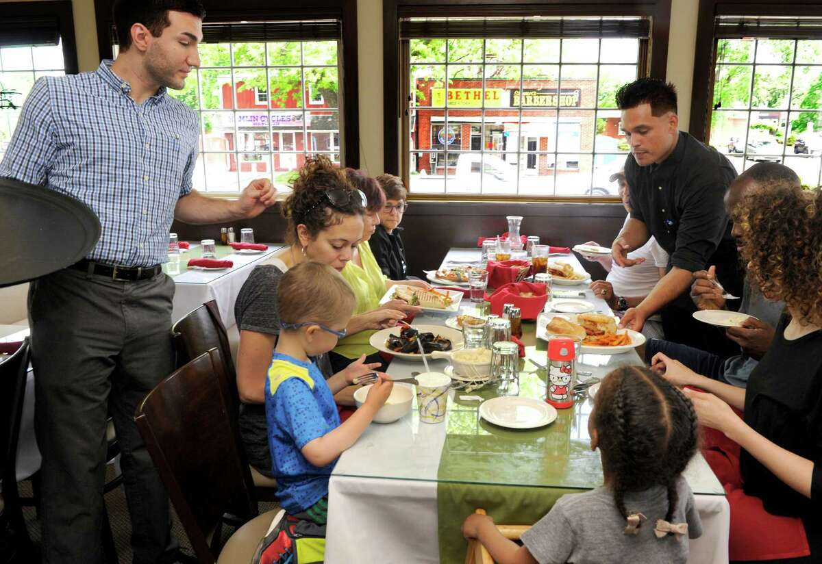 Robert Germinaro, left, general manager and waiter Jose Hernandez serve lunch to the Nunn family of Danbury at Julliano's Monday, May 23, 2016. Jullianos is the new Italian restaurant that opened in downtown Bethel in the spot that was formerly Tonelli's and more recently Parma's.
