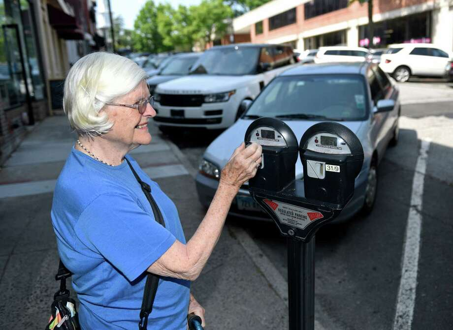 Greenwich resident Elizabeth Burke puts a coin in the parking meter on Greenwich Avenue in downtown Greenwich, Conn. Thursday, June 3, 2016. Photo: Tyler Sizemore / Hearst Connecticut Media / Greenwich Time