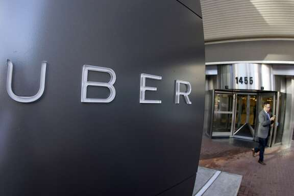 FILE - In this Dec. 16, 2014, file photo a man leaves the headquarters of Uber in San Francisco. Uber said Wednesday, June 1, 2016, that it is getting a massive cash infusion from Saudi Arabia. (AP Photo/Eric Risberg, File)
