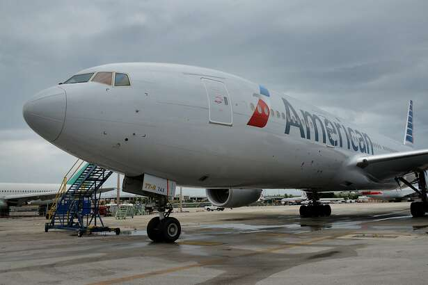 An American Airlines jet parked at a terminal of Miami International Airport in 2014. The world's largest airline plans to stop on-board announcements of connecting gate information as flights prepare to land. MUST CREDIT: Bloomberg photo by Mark Elias.