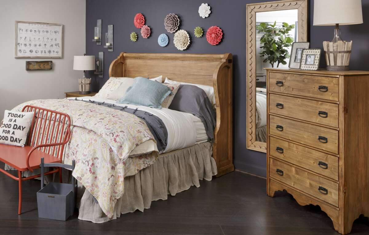 Joanna Gaines' Magnolia Home collection is displayed at Star Furniture similar to the style of Silos, her store in Waco. The bed in this vignette has a headboard styled after a church pew. (Photo courtesy of Star Furniture)