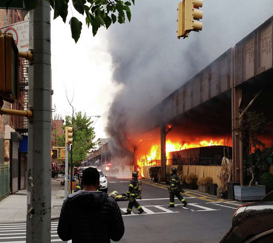In this photo provided by Benjamin Parkin, firefighters battle a blaze at the Metro-North railroad tracks in New York, Tuesday, May 17, 2016. Photo: Benjamin Parkin / Associated Press / Benjamin Parkin