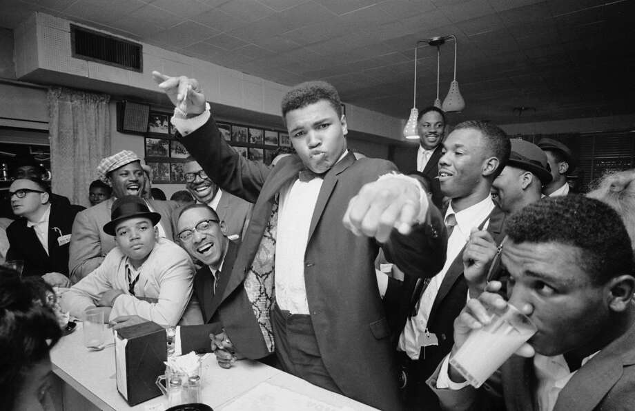 American boxer Classius Clay (later Muhammad Ali) (center), dressed in a tuxedo, holds court at a diner with fans, friends, and admirers after his defeat of Sonny Liston, Miami, Florida, March 1, 1964. Photo by Bob Gomel/The LIFE Images Collection/Getty Images) Photo: Bob Gomel, The LIFE Images Collection/Getty Images