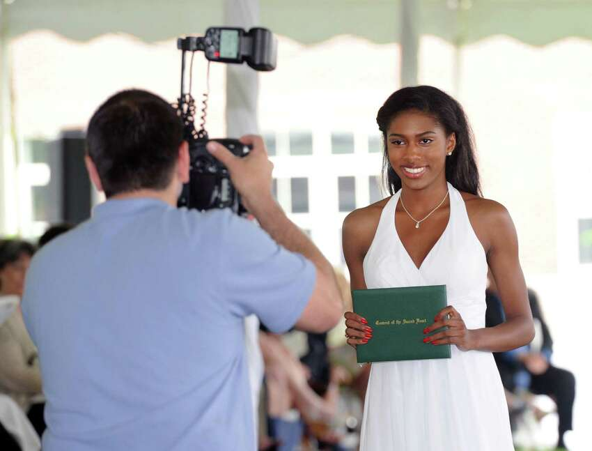Convent of the Sacred Heart's Cheyann Greirson gets her photo taken after receiving her diploma during the commencement at the school in Greenwich, Conn., Friday, June 3, 2016.