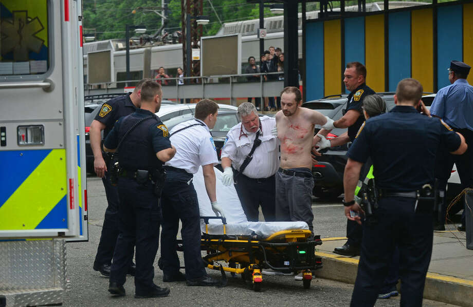 A knife-wielding passenger who was terrorizing fellow commuters on a southbound Metro-North train is arrested by Norwalk and Metro-North police at Rowayton Train Station in Norwalk, Conn. and transported to Norwalk Hopsital by paramedics with self-inflicted knife wounds on Friday, June3, 2016. Photo: Erik Trautmann / Hearst Connecticut Media