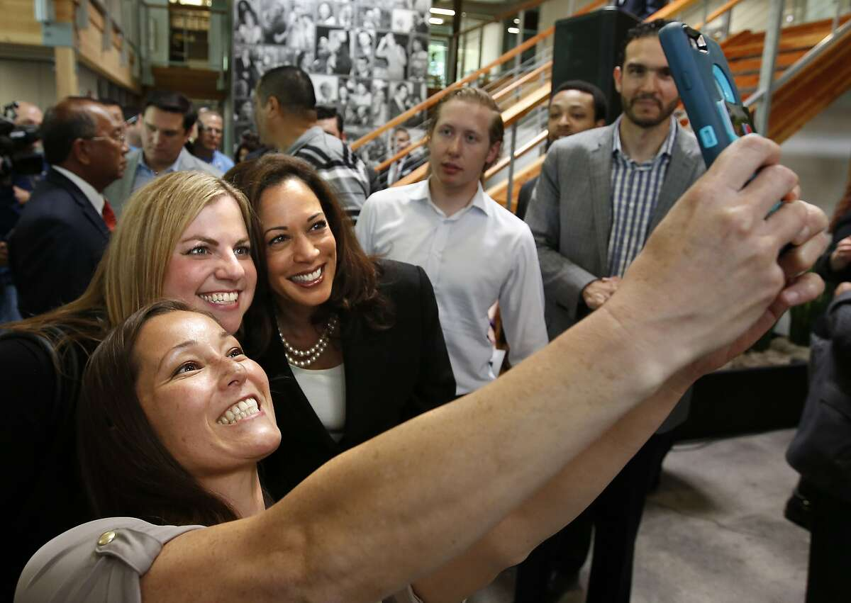Attorney General Kamala Harris, third from left, takes a poto with Alissa Harris, second from left, and Meiling Hunter, left, after a news conference where Gov. Jerry Brown endorsed Harris in the U.S. Senate race, in Sacramento, Calif., Monday, May 23, 2016. Harris is running against fellow Democrat, Rep. Loretta Sanchez, among others, to replace Barbara Boxer who is retiring. (AP Photo/Rich Pedroncelli)