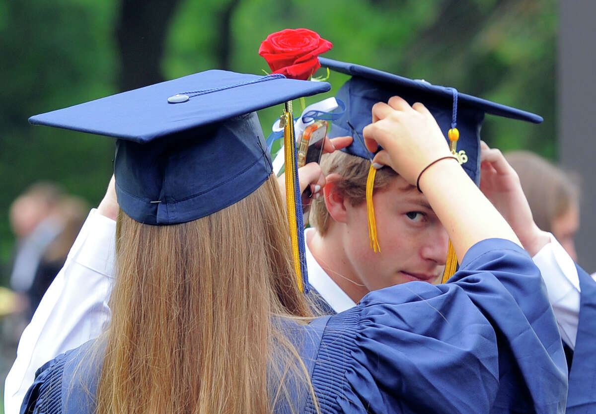 Megan Green of Stamford helps fellow graduate Robby Smithline of Harrison, NY, with his cap prior to the King School commencement at the school in Stamford, Conn., on Friday, June 3, 2016.