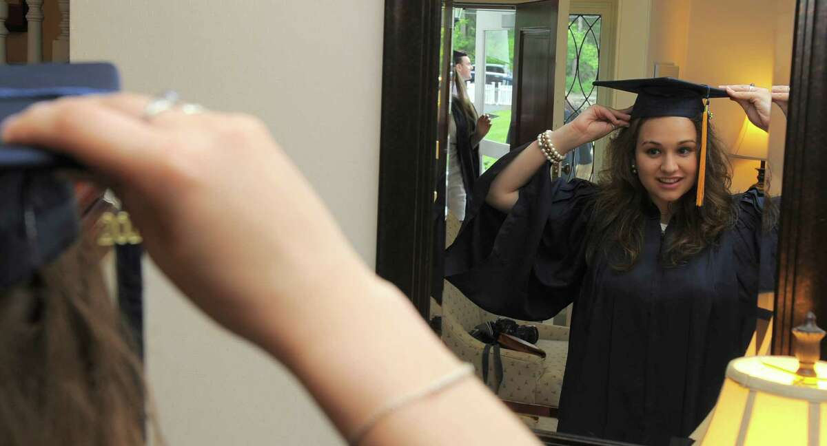 Haley Truglia of Stamford, uses a mirror to adjust her cap prior to the King School commencement at the school in Stamford, Conn., on Friday, June 3, 2016.