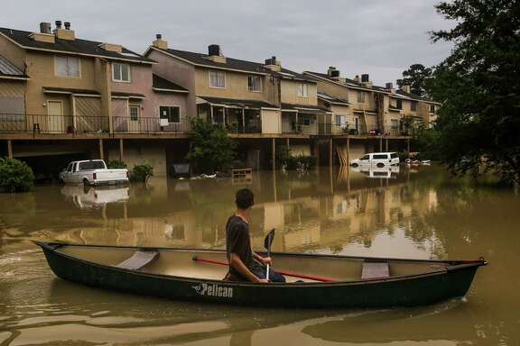 Chance Morgan canoes past flooded townhouses on the way to his Kingwood home on Thursday, June 2, 2016. (Michael Ciaglo / Houston Chronicle)