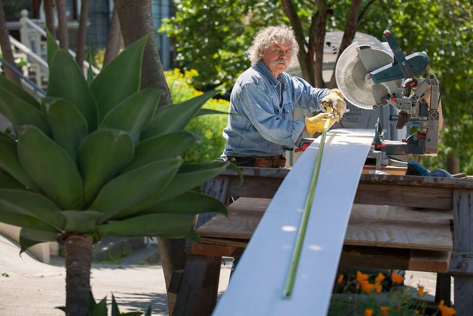 Skeeter Jones measures a plank while working on the facade of a home near 20th and Noe Streets in S.F. He says he has worked on more than 100 houses. Photo: Santiago Mejia, Special To The Chronicle