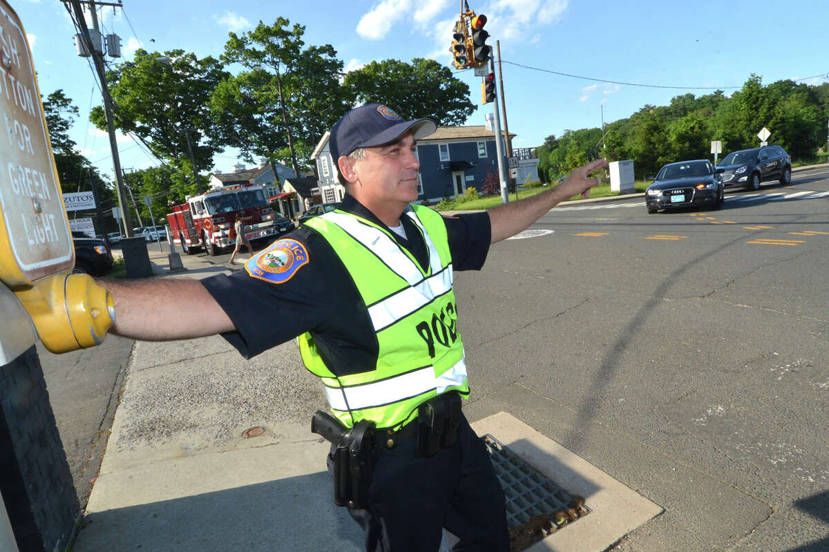 Westport Police Detective Phil Restieri motions to drivers to make the right turn on red onto Bridge st over the Saugatuck River bridge during rush hour traffic on Tuesday May 31 in Westport Conn.