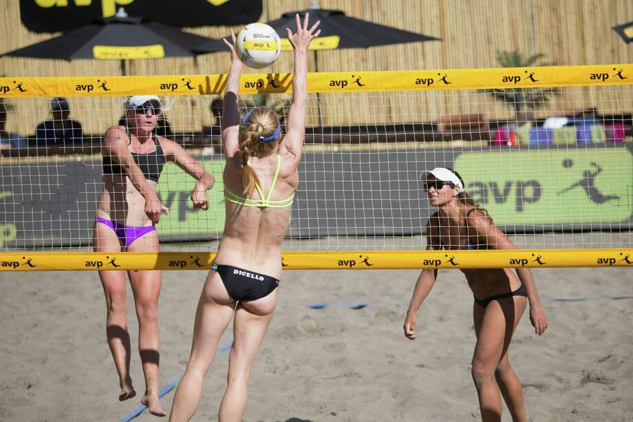 Sarah Day spikes a ball through the hands of her opponent, Kim DiCello, at the AVP Seattle Open in the stadium at Lake Sammamish State Park on Friday, June 3, 2016.  Top-seeded DiCello and her partner Kendra VanZwieten won this winner's bracket quarterfinal over Day and Jessica Stubinski (right), 16-21, 21-17, 15-12. Photo: LACEY YOUNG, SEATTLEPI.COM / SEATTLEPI.COM