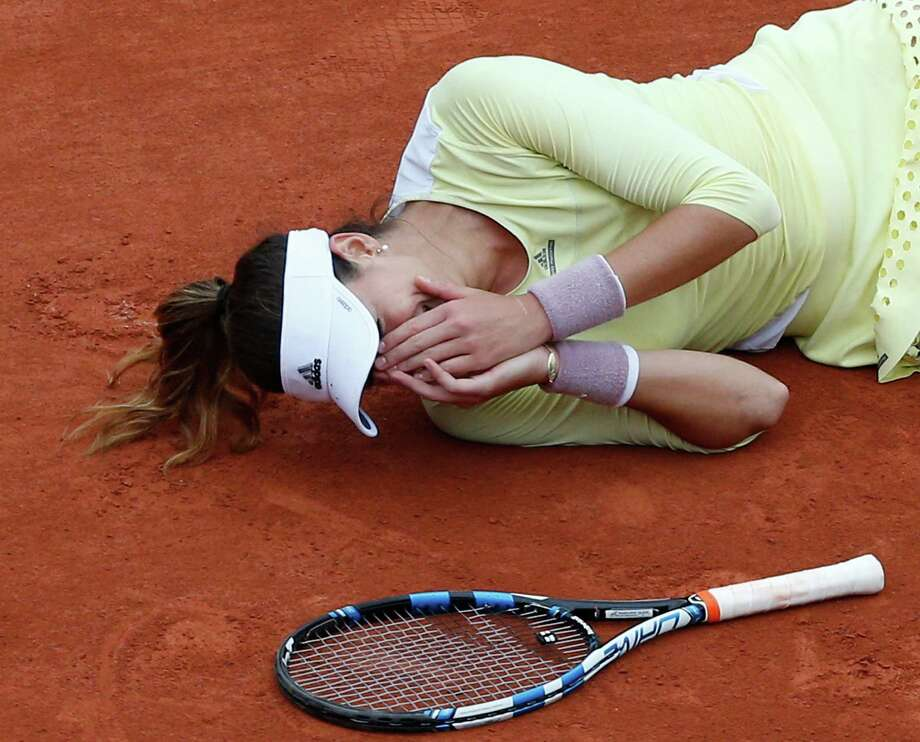 Spain's Garbine Muguruza lies on the clay as she defeats Serena Williams of the U.S.  during their final match of the French Open tennis tournament at the Roland Garros stadium, Saturday, June 4, 2016 in Paris.  Muguruza won 7-5, 6-4. Photo: Christophe Ena, AP / AP