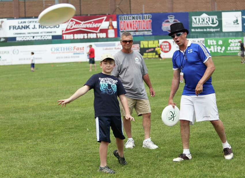 Ayden Scinto, 6, and his grandfather Tim Horton get a lesson from Skip Kuhn of Hall of Famers Disc Camp during the 2016 Circles on Sounds Frisbee Festival, which opened at the Ballpark at Harbor Yard in Bridgeport, Connecticut on Saturday, June 4, 2016. The festival features frisbee golf, frisbee clinics and frisbee catching dogs.