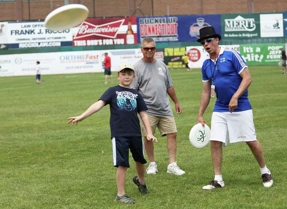 Ayden Scinto, 6, and his grandfather Tim Horton get a lesson from Skip Kuhn of Hall of Famers Disc Camp during the 2016 Circles on Sounds Frisbee Festival, which opened at the Ballpark at Harbor Yard in Bridgeport, Connecticut on Saturday, June 4, 2016. The festival features frisbee golf, frisbee clinics and frisbee catching dogs. Photo: Danielle Robinson Calloway / For Hearst Connecticut Media / Connecticut Post Freelance