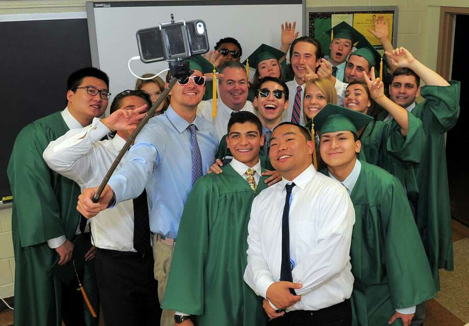 Seniors gather for a group selfie with  home room advisor John Casey prior to Trinity Catholic High School Class of 2016 commencement at the school in Stamford, Conn., on Saturday, June 4, 2016. Photo: Matthew Brown, Hearst Connecticut Media / Stamford Advocate