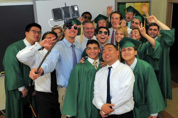 Seniors gather for a group selfie with  home room advisor John Casey prior to Trinity Catholic High School Class of 2016 commencement at the school in Stamford, Conn., on Saturday, June 4, 2016.