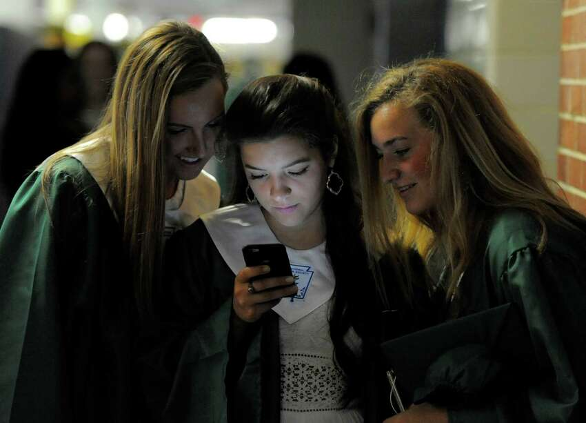 From left, Emma Connolly, Christine Handler and Jenalynn Fumega check pictures they would share on social media with friends prior to Trinity Catholic High School Class of 2016 commencement at the school in Stamford, Conn., on Saturday, June 4, 2016.