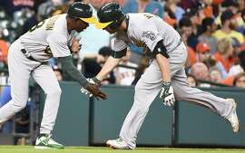 Oakland Athletics' Danny Valencia, right, low-fives third base coach Ron Washington after hitting a solo home run off Houston Astros starting pitcher Collin McHugh during the sixth inning of a baseball game, Saturday, June 4, 2016, in Houston. (AP Photo/Eric Christian Smith)