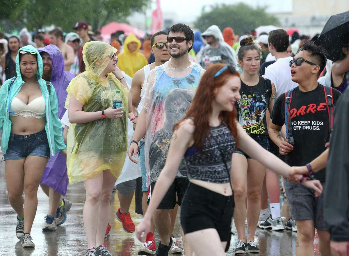 People walk between stages in the rain at Free Press Summer Fest, at NRG, Saturday, June 4, 2016, in Houston.