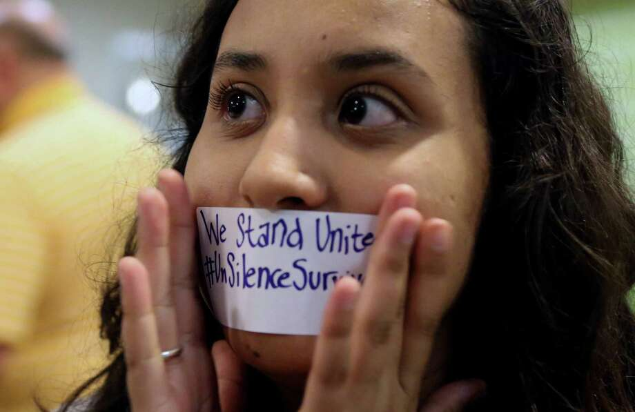 Baylor junior Julieth Reyes cover her mouth with tape during a rally a rally of current and former Baylor students warning of sexually assaults on and off campus, Friday, June 3, 2016, in Waco, Texas. Calling the rally Un-silence the Survivors, they read an open letter to the administration about improvements on how the school should handle sexual assaults after observing a moment of silence. (Rod Aydelotte/Waco Tribune Herald, via AP) Photo: Associated Press / Waco Tribune Herald