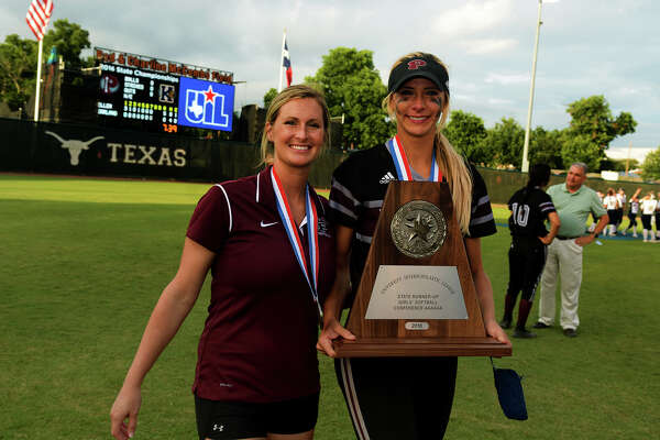 Pearland Asst. Coach Tiffany Neal, left, and her sister, senior pitcher Alyssa Denham, leave the field with the Class 6A runner-up trophy in hand after the Lady Oiler's 5-0 loss to the Keller Lady Indians at the 2016 UIL Softball State Championships at McCombs Field in Austin on Saturday, June 4, 2016. (Photo by Jerry Baker/Freelance)