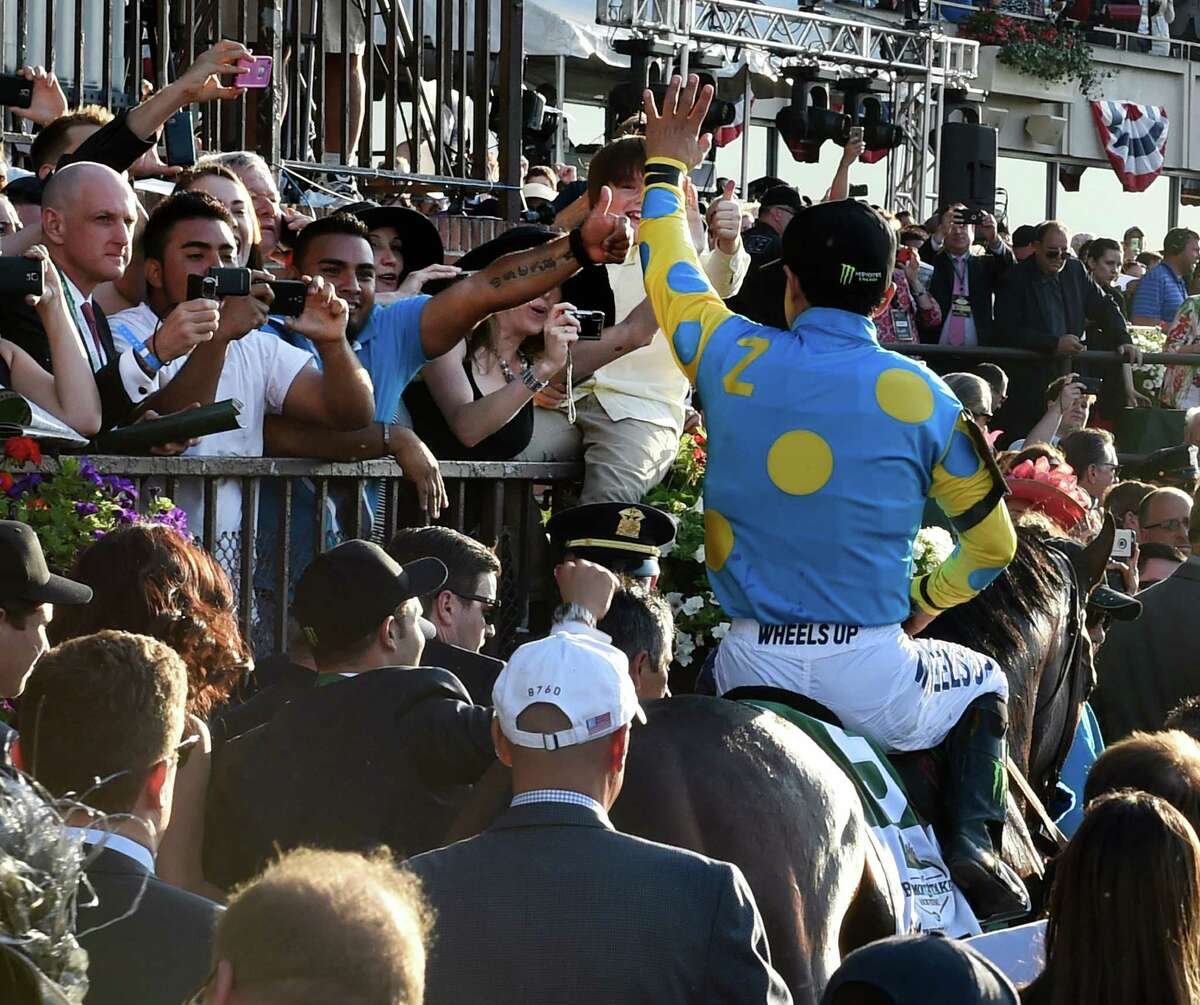 American Pharoah enters the winner's circle with jockey Victor Espinoza as a crowd of onlookers rejoice. Fans will not be allowed to take in the 2020 edition of the race. (Skip Dickstein/Times Union)