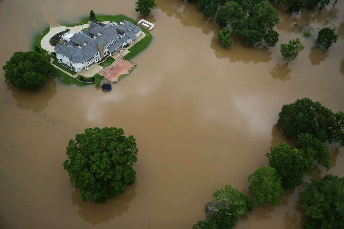 Floodwaters from the Brazos River surround a home on Saturday after heavy rains pounded the area again last week.