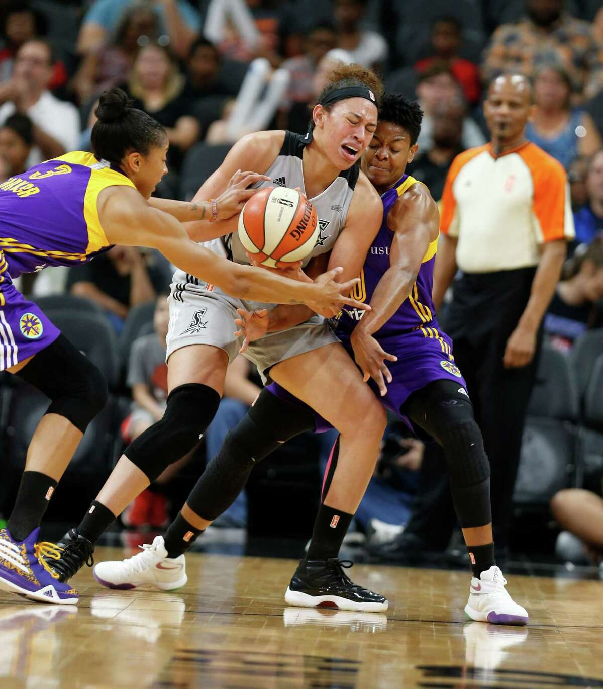 The Stars' Dearica Hamby (center) steals rhe ball from the Sparks' Candace Parker (left) as Alana Beard tries to get it back.