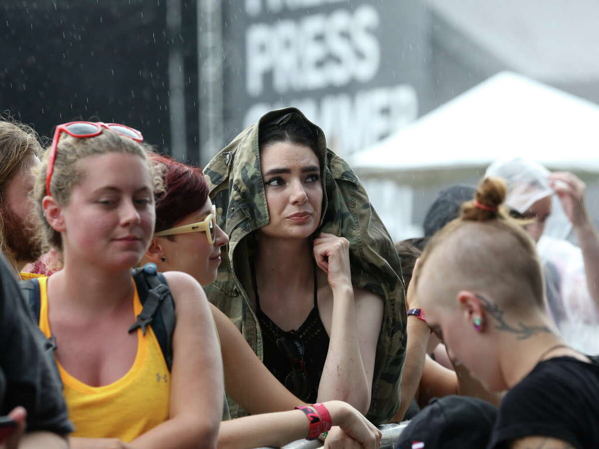Caroline Hubble waits in the rain for Gogol Bordello to perform at Free Press Summer Fest, at NRG, Saturday, June 4, 2016, in Houston.
