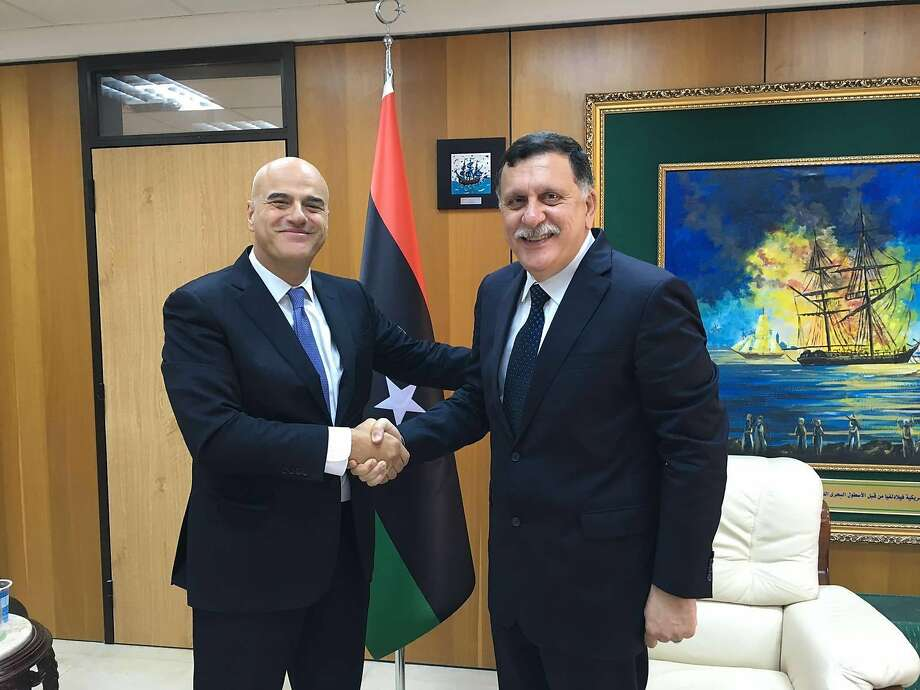 Italian oil giant Eni CEO Claudio Descalzi, left, and and Libya's new prime minister, Fayez al-Serraj shake hands in Tripoli, Libya, Saturday, June 4, 2016. Descalzi has acquired a stake in the world's fourth-largest oil processing plant.  NEXT: See the world's largest refineries.    Photo: Associated Press