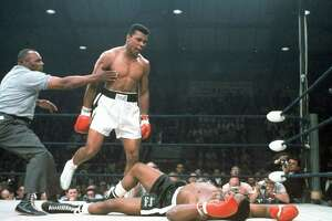 In this May 25, 1965, file photo, heavyweight champion Muhammad Ali is held back by referee Joe Walcott, left, after Ali knocked out challenger Sonny Liston in the first round of their title fight in Lewiston, Maine. Ali transcended the sport. If you were a black kid growing up in the 1960's and 1970's Ali's words, his style, his audacity was liberating and uplifting.