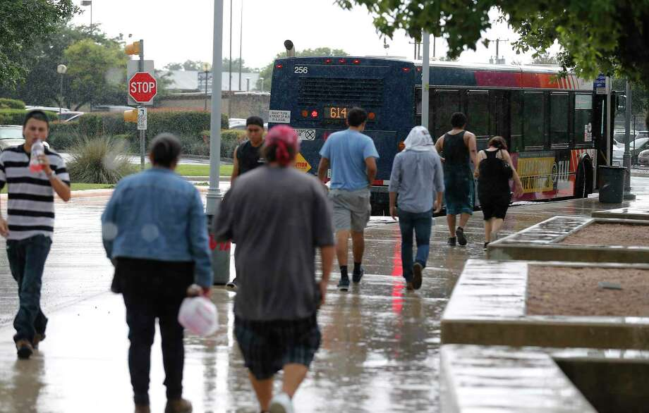 VIA patrons walk to a bus at VIA's Kel-Lac Transit Center in this 2016 file photo.