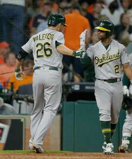 HOUSTON, TX - JUNE 04: Danny Valencia #26 of the Oakland Athletics receives congratulations from Khris Davis #2 after hiting a home run in the sixth inning against the Houston Astros at Minute Maid Park on June 4, 2016 in Houston, Texas. (Photo by Bob Levey/Getty Images)