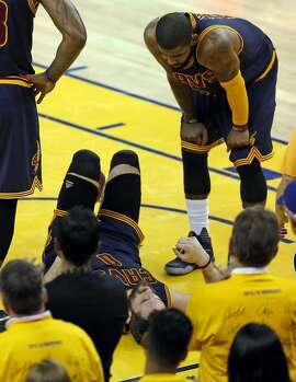 Cleveland Cavaliers' Kyrie Irving looks down at Kevin Love after he was elbowed in the head by Golden State Warriors' Harrison Barnes in 2nd quarter of Warriors' 110-77 win in Game 2 of NBA Finals at Oracle Arena in Oakland, Calif., on Sunday, June 5, 2016.