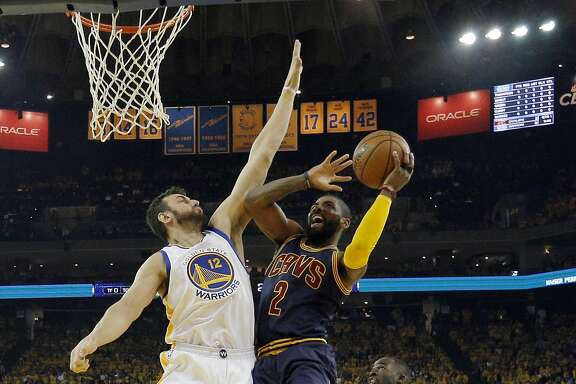 Andrew Bogut (12) defends against a shot by Kyrie Irving (2) in the second half as the Golden State Warriors played the Cleveland Cavaliers in Game 2 of the NBA Finals at Oracle Arena in Oakland, Calif., on Sunday, June 5, 2016. The Warriors defeated the Cavaliers 104-89.