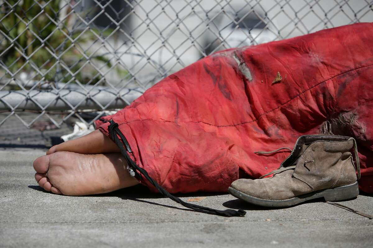 A man's feet stick out of a sleeping bag as he lays on Utah Street on Friday, May, 27, 2016 in San Francisco, California.