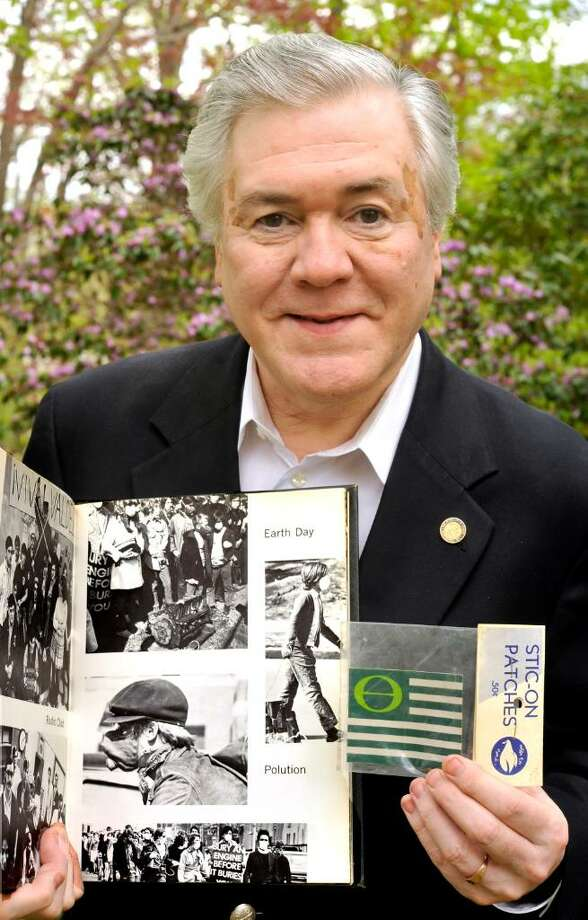 Jim Dyer holds his 1970 Western Connecticut State College yearbook that shows how the first Earth Day was observed and an Earth Day patch also from 1970, outside hid Danbury home on Wednesday, April 21, 2010. Photo: Michael Duffy / The News-Times