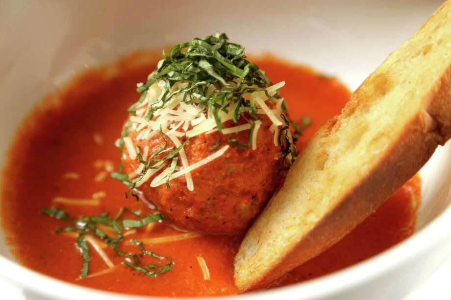 A big meatball is served in a spicy tomato sauce with crusty bread. Photo: Gary Coronado, Staff / © 2015 Houston Chronicle