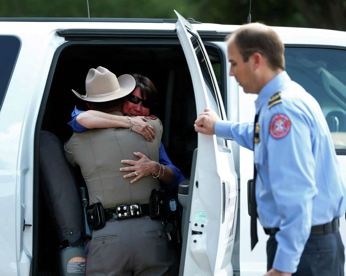 Denise Corliss, handler for Bretagne, the last surviving search and rescue dog from 9/11, gets a hug from a trooper with the Texas Highway Patrol, after Bretagne's body was loaded into a Texas Task Force 1 vehicle, and taken to Texas A&M, after she was brought into the Fairfield Animal Hospital, Monday, June 6, 2016, in Cypress, to be euthanized.