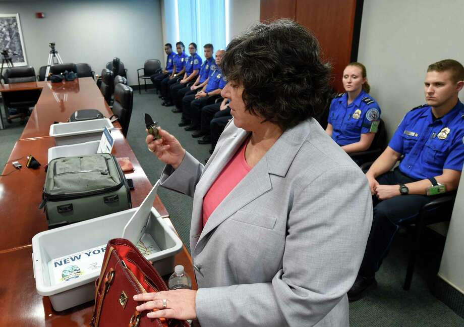 Lisa Farstein of the TSA demonstrates what not to take to the airport before check-in during a press briefing at the Albany International Airport June 6, 2016 in Colonie, N.Y. (Skip Dickstein/Times Union) Photo: SKIP DICKSTEIN / 40036852A