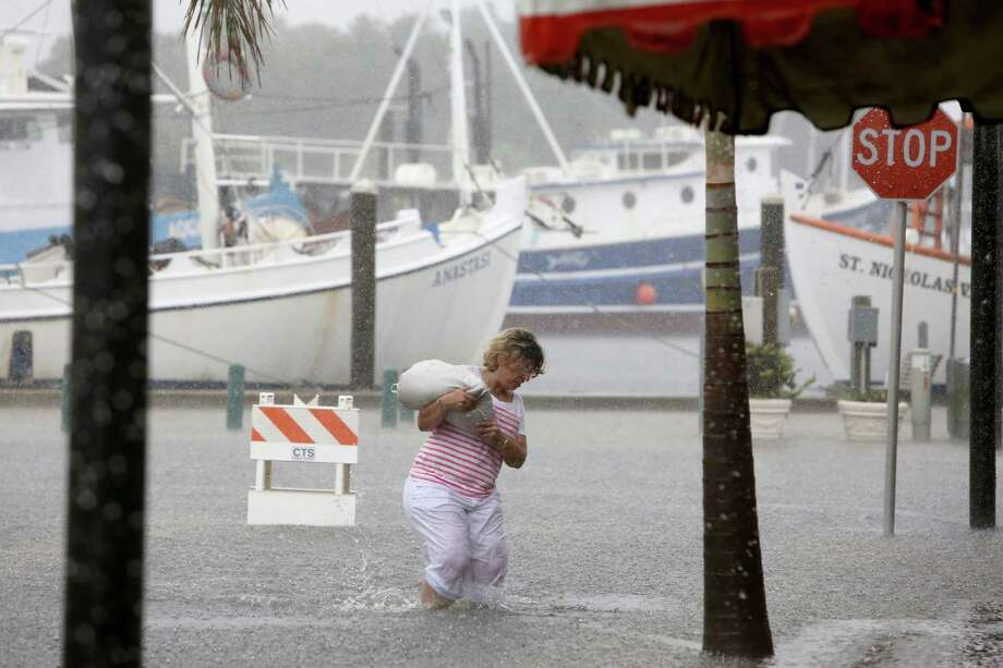 Kelly Spiliotis lugs a sandbag across flooded Athens Street in Tarpon Springs, Fla., on Monday en route to her shop as Tropical Storm Colin inundated Florida's west coast. Photo: Douglas R. Clifford, MBI / Tampa Bay Times