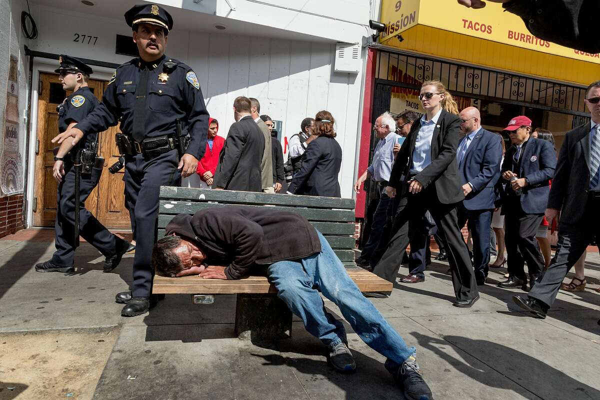 A man sleeps on a bench as Vermont Senator Bernie Sanders walks down mission street flanked by SFPD and Secret Service officers in San Francisco, Calif., Tuesday, June 6, 2016.